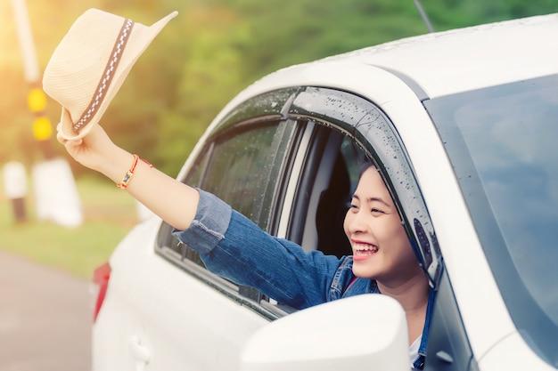 Entspannte glückliche frau auf den sommer roadtrip reiseferien, die heraus autofenster der naturansicht betrachten