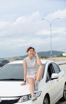 Entspannte, glückliche, zierliche frau im reiseurlaub. auf dem auto sitzen. lifestyle- und people-konzept.