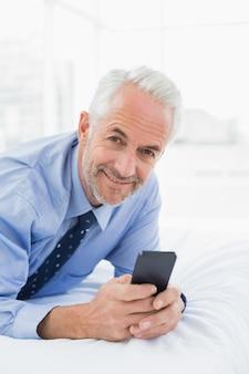 Entspannte gut gekleidete mannversenden von sms-nachrichten im bett