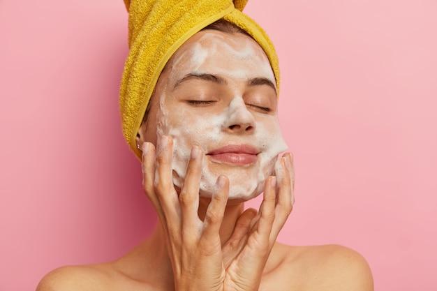 Entspannte hübsche frau kümmert sich um ihr aussehen, wäscht das gesicht mit angenehmem gesichtsgel oder seife, entfernt alle poren, hält die augen vor vergnügen geschlossen und wird hygienisch behandelt