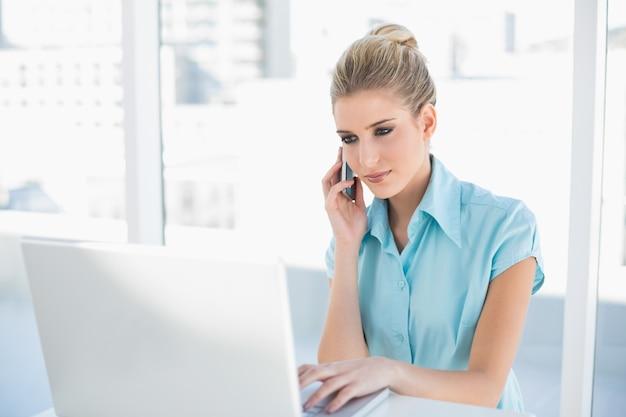 Entspannte intelligente geschäftsfrau am telefon bei der anwendung des laptops