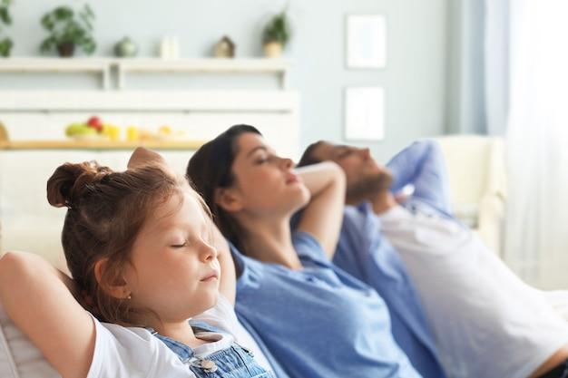 Entspannte junge familie, die sich zu hause auf einem bequemen sofa ausruht und von einem neuen zuhause träumt, glückliche junge eltern mit kleiner tochter entspannen sich beim entspannen oder meditieren.