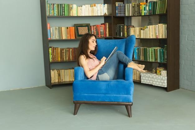 Entspannte junge frau, die auf sofa mit tablette sitzt