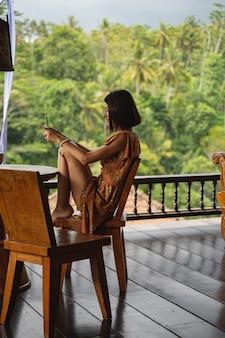 Entspannte junge frau, die in halbposition auf einem holzstuhl sitzt, während sie online mit ihrem kollegen chattet