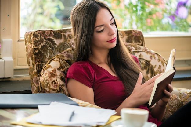 Entspannte junge frau, die sitzt, während sie ein interessantes buch drinnen zu hause liest