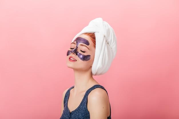 Entspannte junge frau, die spa-behandlung auf rosa hintergrund tut. studioaufnahme des erfreuten mädchens mit der gesichtsmaske, die mit geschlossenen augen aufwirft.