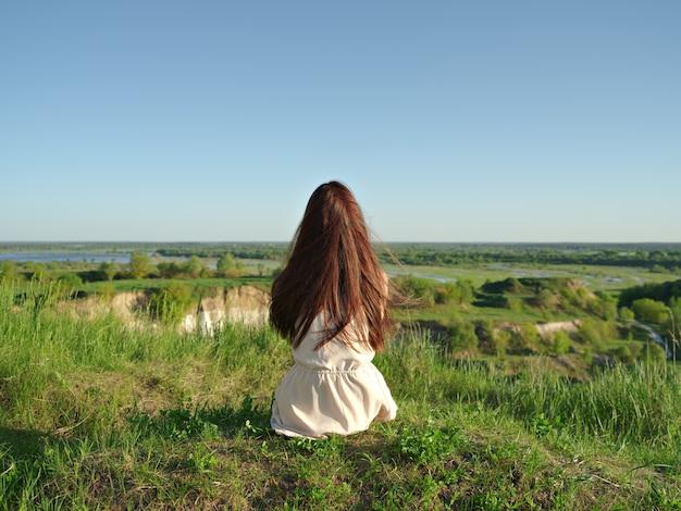 Entspannte junge frau mit blick in die aussicht. friedliches mädchen, das an einer klippe sitzt und die landschaft genießt. - im freien