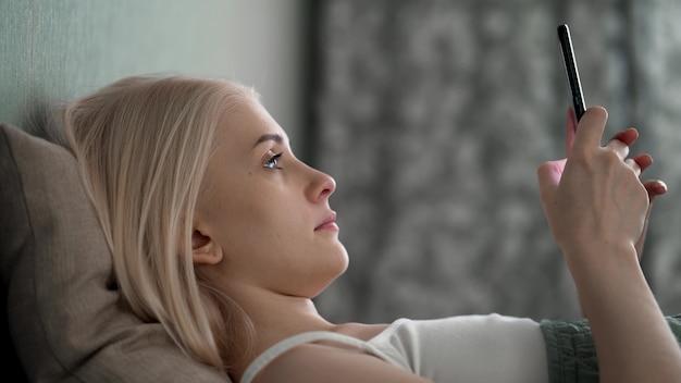 Entspannte junge frau mit smartphone, die in sozialen medien surft, nachrichten überprüft, handyspiele spielt oder sms-nachrichten auf dem sofa sendet. tausendjährige dame, die zeit zu hause mit zell-gadget-technologie verbringt.