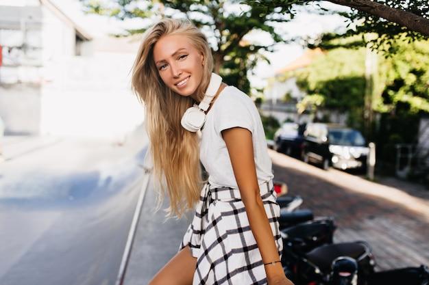 Entspannte junge frau mit sonnenbräune, die mit erstaunlichem lächeln posiert, während sie in der nähe der straße steht.