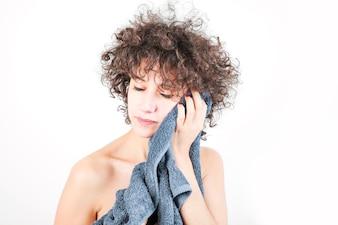 Entspannte junge Frau wischt ihr Gesicht mit Tuch gegen weißen Hintergrund ab
