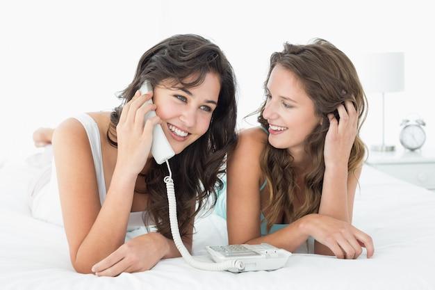 Entspannte junge freundinnen, die telefon im bett verwenden