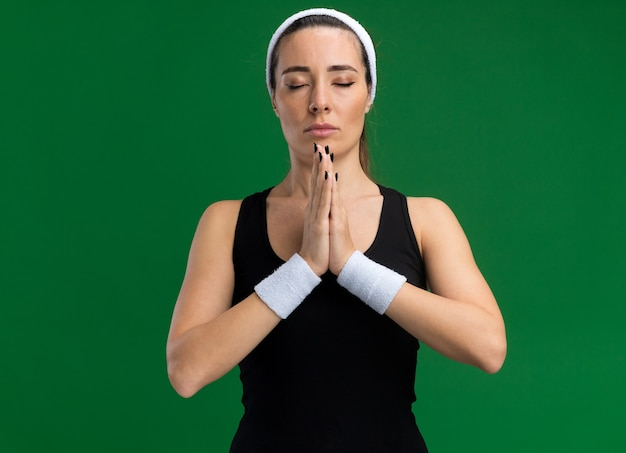 Entspannte junge hübsche sportliche frau mit stirnband und armbändern, die die hände mit geschlossenen augen zusammenhält