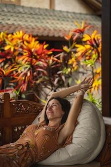 Entspannte junge internationale weibliche person, die sich ausruht und ihren urlaub in einem exotischen land genießt