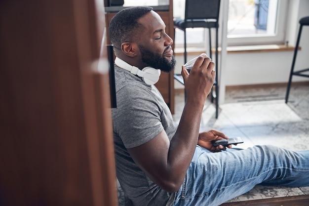 Entspannte junge männliche person, die leckeren kaffee genießt