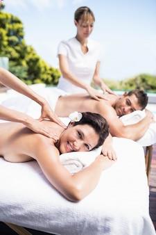 Entspannte junge paare, die eine rückenmassage vom masseur in einem badekurort erhalten