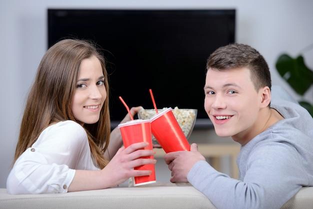 Entspannte junge paare, die fernsehen und soda trinken.