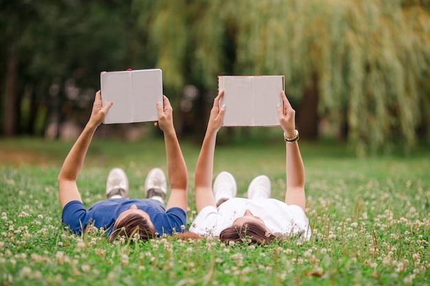 Entspannte junge paarlesebücher beim lügen auf gras