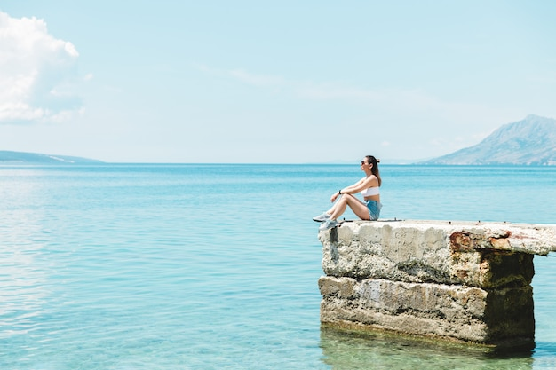 Entspannte junge touristin auf see, die am strand sitzt, frei atmet und nach langer sperrung in die ferne schaut