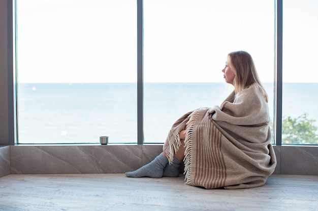 Entspannte kaukasische frau, die auf einem warmen boden in socken eingewickelt in einer woolen decke nahe dem großen fenster im licht sitzt. herbststimmung, wärme und gemütlichkeit.