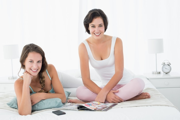 Entspannte lächelnde freundinnen mit zeitschrift im bett