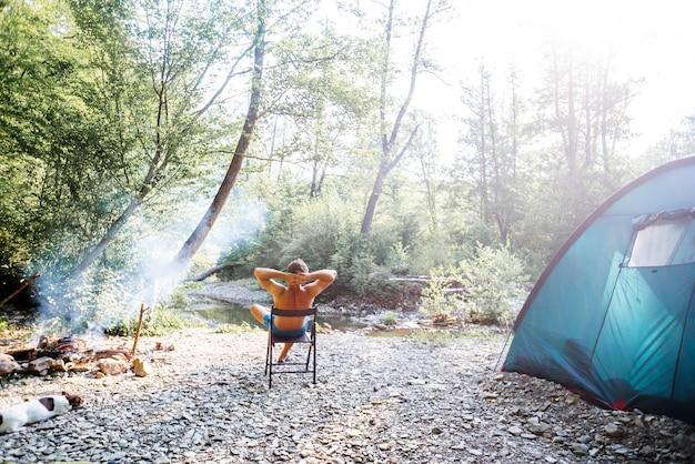 Entspannte männer sitzen außerhalb des zeltes, während sie an einem sonnigen tag in der nähe des bergflusses campen