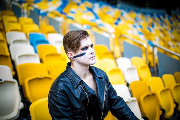 Entspannte mode für männer in lederjacke posiert beim sitzen im stadion Premium Fotos