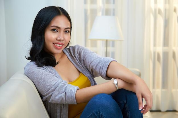 Entspannte philippinische frau, die auf couch sitzt