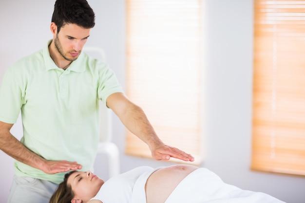 Entspannte schwangere frau, die reiki behandlung erhält
