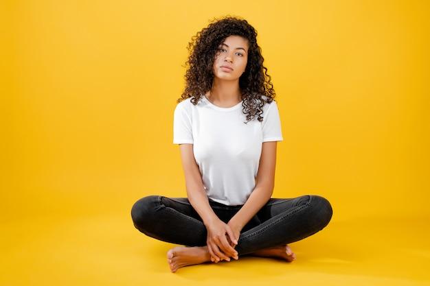 Entspannte schwarze frau, die in der yogahaltung getrennt über gelb meditiert