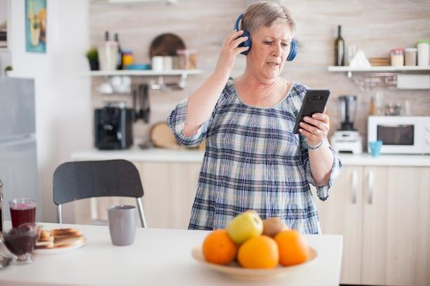 Entspannte seniorin, die beim frühstück in der küche musik über kopfhörer hört. ältere menschen tanzen, lustiger lebensstil mit moderner technologie