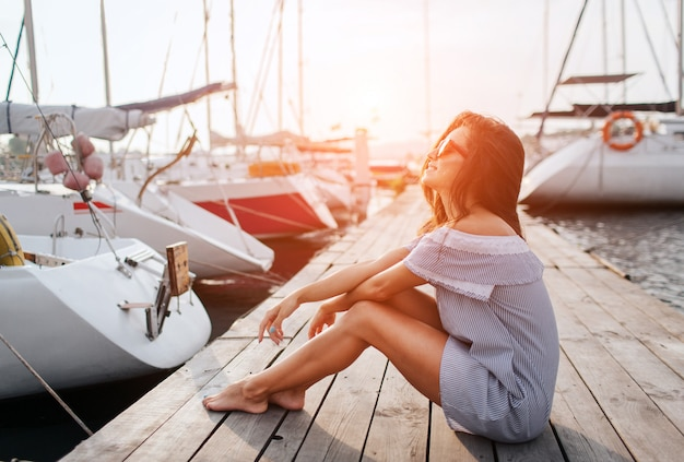 Entspannte und friedliche junge frau sitzt am pier. sie hält beine und hände zusammen. sie trägt eine sonnenbrille und ein gestreiftes kleid. junge frau posieren vor der kamera.