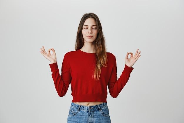 Entspannte und ruhige attraktive frau meditiert mit seitlich gespreizten händen, geschlossenen augen, macht yoga