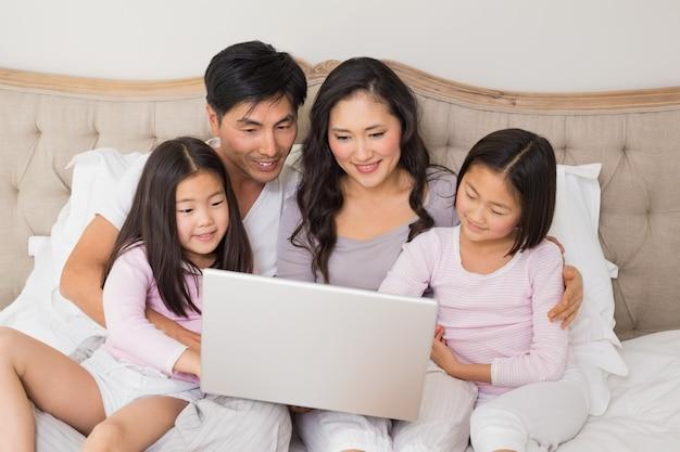 Entspannte vierköpfige familie unter verwendung des laptops im bett