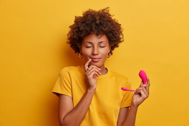 Entspannte zufriedene frau, die gerne einen intelligenten vibrator kauft, die vibrationsgeschwindigkeit nicht über die sprachsteuerung steuern kann, smartphone-app verwendet, isoliert auf gelber wand. drahtloser ferngesteuerter klitorisstimulator
