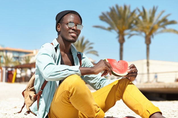 Entspannter abenteurer, der frische reife wassermelone isst