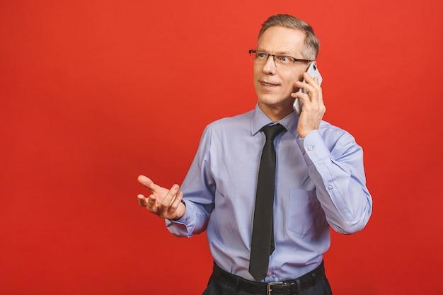 Entspannter älterer geschäftsmann in der formellen verwendung des smartphones lokalisiert auf roter wand. porträt eines glücklichen reifen geschäftsmannes mit handy. zufriedener anführer, der e-mails mit speicherplatz überprüft.