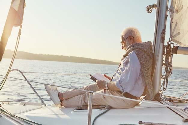 Entspannter älterer mann, der ein buch liest, während er auf der seite des segelboots oder des yachtdecks sitzt