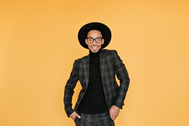 Entspannter afrikanischer kerl im karierten vintage-anzug, der auf gelber wand lächelt. aufgeregter schwarzer junger mann im hut, der spaß während des fotoshootings hat.