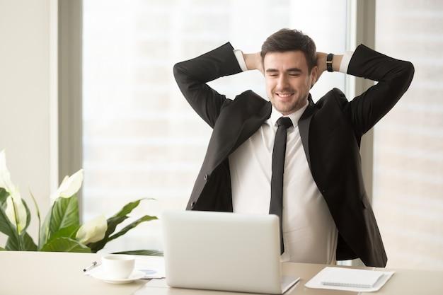 Entspannter angestellter, der das ergebnis der guten arbeit erledigt genießt