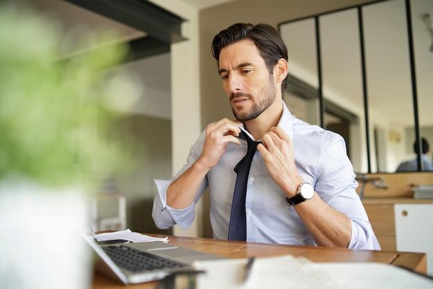 Entspannter attraktiver geschäftsmann, der bindung rückgängig macht und im modernen büro arbeitet