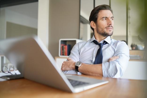 Entspannter attraktiver geschäftsmann, der im modernen büro arbeitet
