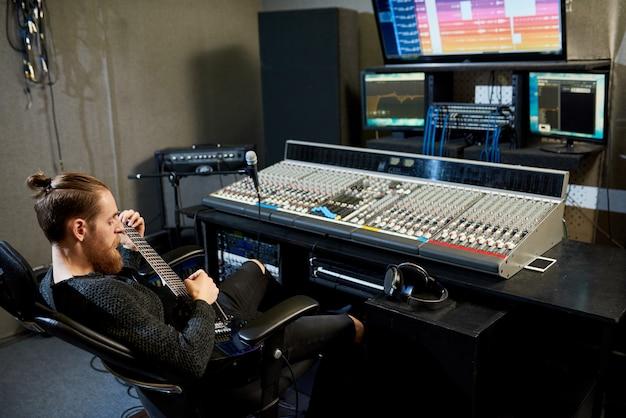 Entspannter audioingenieur, der pause macht, um gitarre zu spielen