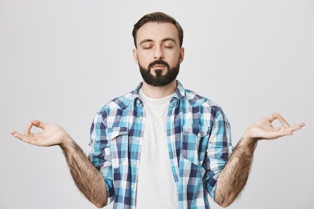 Entspannter bärtiger mann meditiert, praktiziert yoga