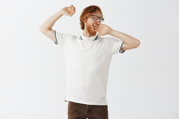 Entspannter bärtiger rotschopf, der mit brille gegen die weiße wand posiert