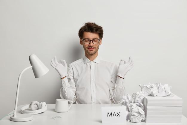 Entspannter bärtiger stilvoller mann im weißen formellen outfit meditiert am gemütlichen arbeitsplatz