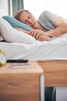 Entspannter erwachsener mann, der sein kissen umarmt, während er zu hause seinen gemütlichen schlaf im bett genießt