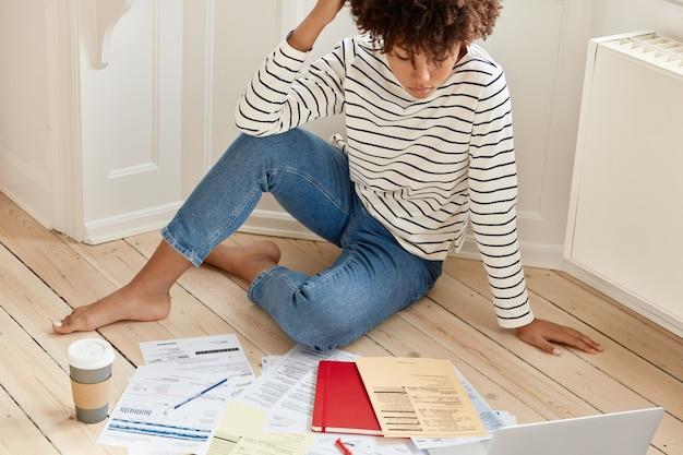 Entspannter freiberufler in gestreiftem pullover und jeans