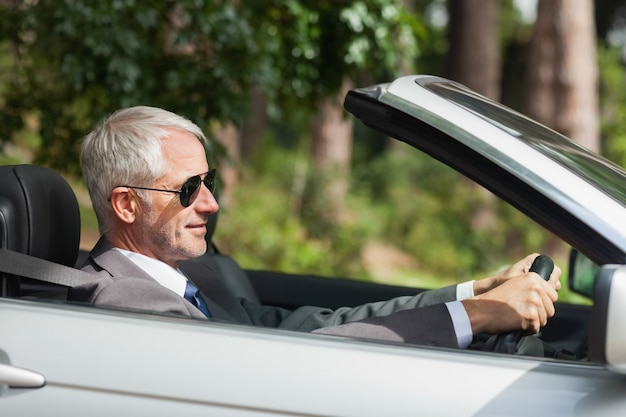 Entspannter geschäftsmann, der noblen cabriolet fährt