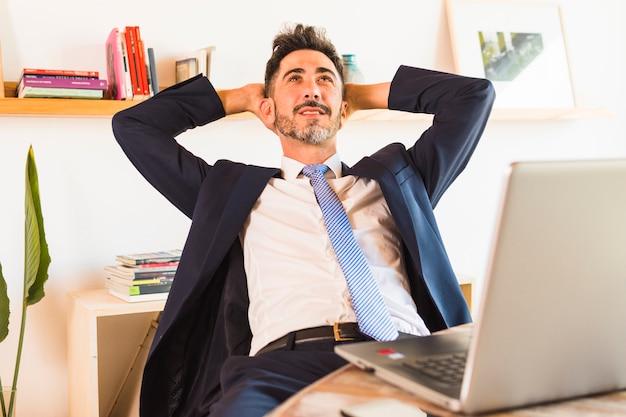 Entspannter geschäftsmann, der oben mit seinem handy auf tabelle schaut