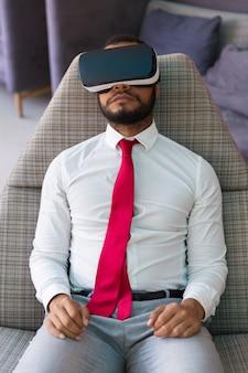 Entspannter geschäftsmann, der virtuellen inhalt genießt